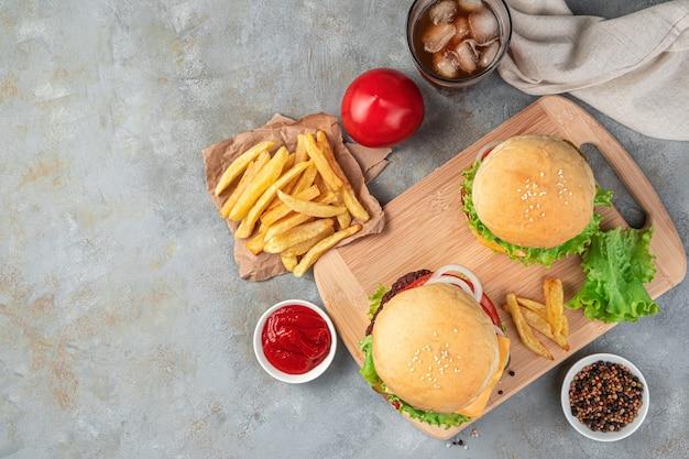 灰色の背景にハンバーガー、フライドポテト、コーラ。ファストフード。上面図、コピースペース。