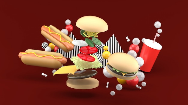 Hamburgers, hot dogs and soft drinks among colorful balls on red. 3d rendering.