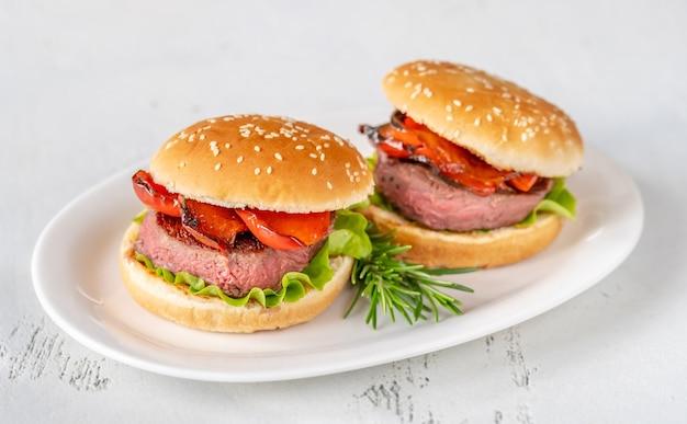 白いサービングプレートにグリルしたコショウのハンバーガー