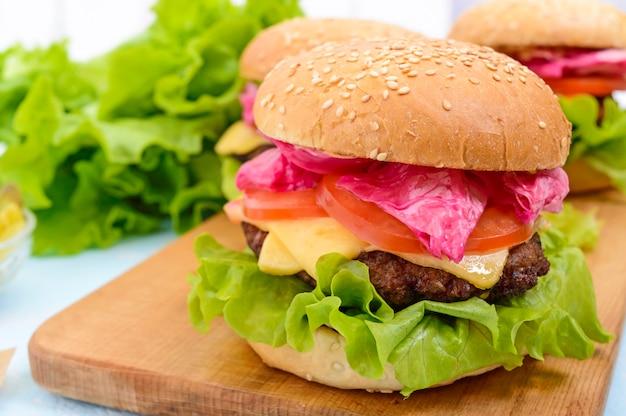 육즙이 많은 커틀릿, 토마토, 절인 양배추와 오이, 치즈, 녹색 양상추 잎, 부드러운 번이 들어간 햄버거