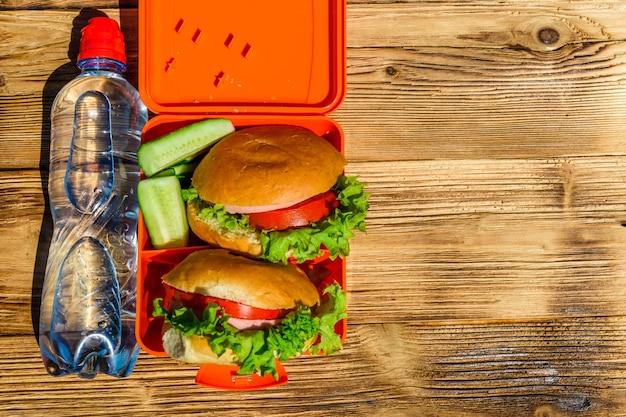 Гамбургеры с салатом в ланчбоксе и бутылкой воды на деревенском деревянном столе. вид сверху