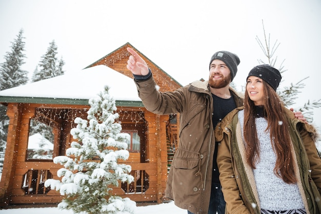 Hamdsome smiling bearded young man stading with his girlfriend and pointing away near log cabin