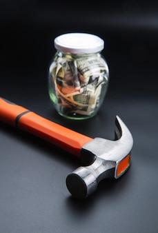 Hammer against jar full of dollars, money saving