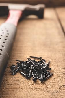 나무 테이블에 망치와 검은 손톱. 오래된 도구. 공간을 복사하십시오.