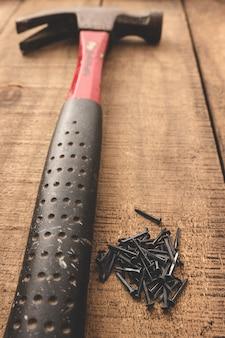 나무 테이블에 망치와 검은 손톱. 오래된 도구.