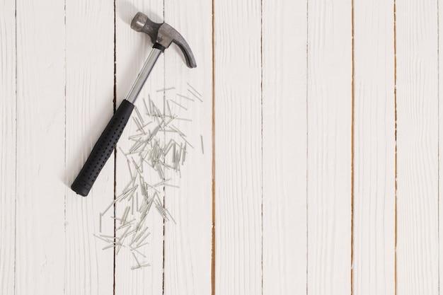 Молоток и гвозди на белой деревянной поверхности