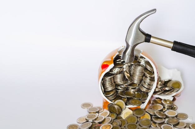Hammer breaking piggy bank with thai baht coins on white background