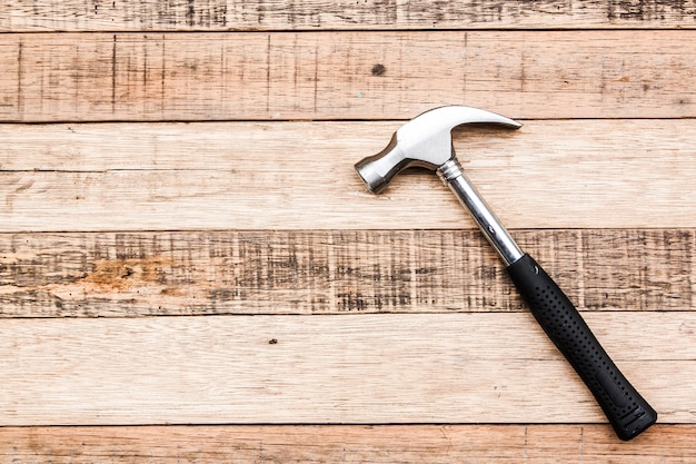 Hammer carpenter tool on wood background