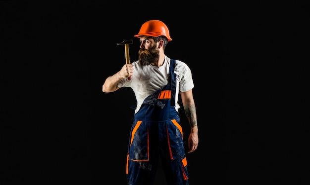 망치 망치. 헬멧, 망치, 핸디, 안전모를 쓴 빌더. 공간을 복사합니다. 검은 배경에 고립 수염된 작성기입니다. 수염을 기른 수염 난 남자 노동자, 건물 헬멧, 단단한 모자.