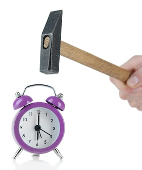Hammer in hand and alarm clock on white