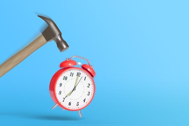 青い背景にモーションブラーとコピースペースで赤い目覚まし時計を打つハンマー。