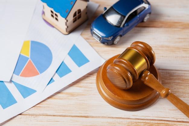 Молоток, дом и автомобиль на деревянной сцене. концепция судебного разбирательства