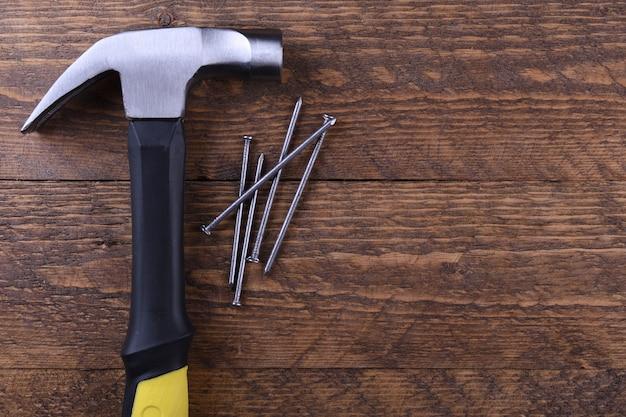Молоток утюг и гвозди на деревянный стол