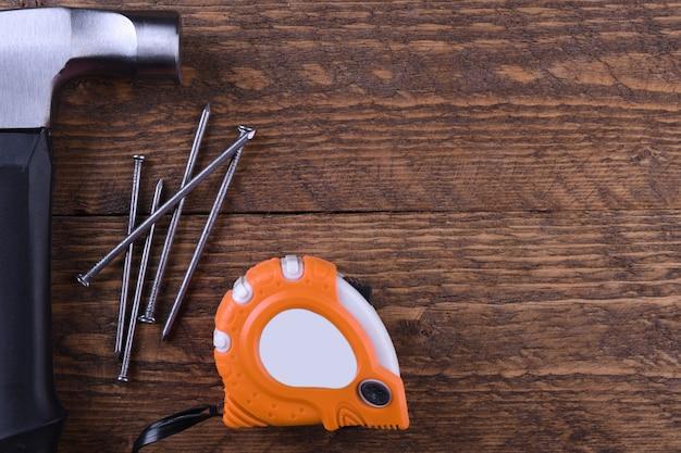 ハンマー鉄、センチメートルテープ、木製テーブルの上の釘