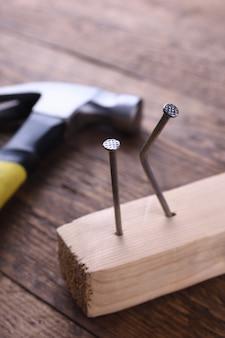 Молоток железный, сантиметровая лента и гвозди на деревянном столе