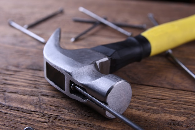 Hammer iron, centimeter tape and nails on wooden table