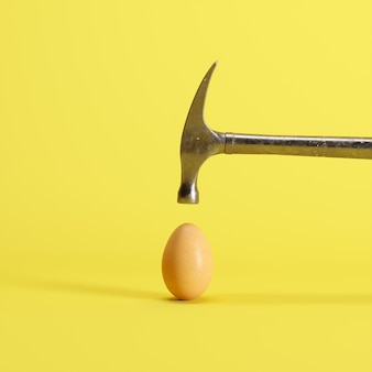 Hammer is hitting on an egg with yellow background