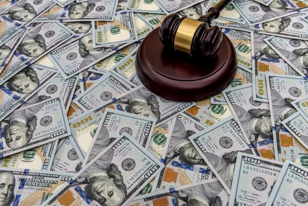 Молоток судьи на фоне крупной суммы долларов