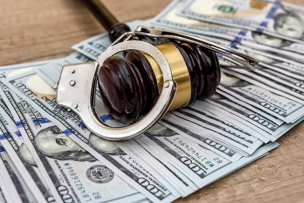 Молоток судьи, наручники и доллары на деревянном столе крупным планом