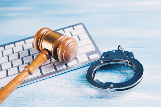 Hammer on the keyboard and handcuffs. cybercrime