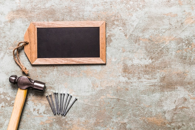 Hammer and nails with blank slate tag over the rustic backdrop