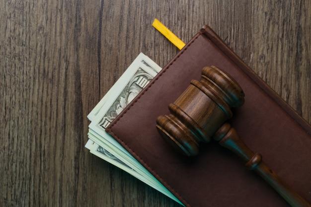 Молоток судьи на папке с деньгами за деревянным столом
