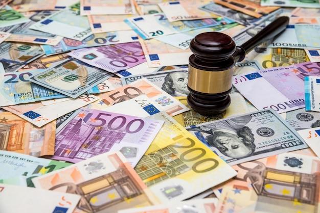Молоток судьи на фоне банкнот доллара и евро