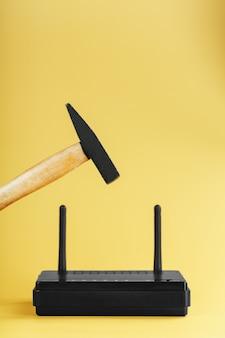 노란색 배경에 파괴를 위해 wi-fi 라우터 위로 망치