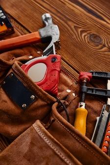 망치, 스테이플러 및 스크루 드라이버, 측정 테이프 및 나무 테이블에 가죽 케이스에 쇠톱