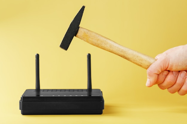 Hammer over the wi-fi router for destruction on a yellow background.