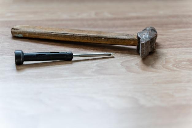コピースペースのある木製の床の背景に木製のハンドルとプレーンスロットドライバーを備えたハンマー。