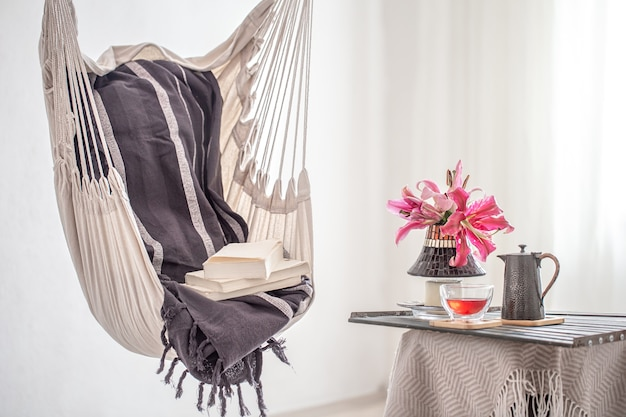 A hammock chair in boho style wiht a books and teapot and cup of tea. the concept of rest and home comfort.