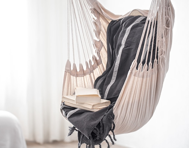 A hammock chair in boho style with a stack of books. the concept cozy place to relax at home.