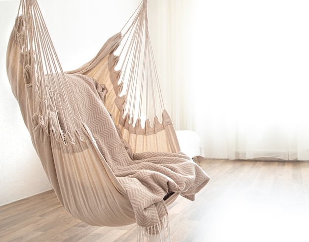 A hammock chair hangs in the room. cozy place to relax at home.