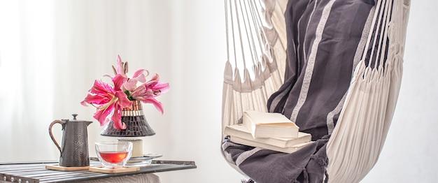 本とティーポットとお茶のカップと自由奔放に生きるスタイルのハンモックチェア。休息と家庭の快適さの概念。