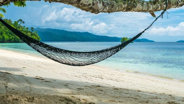 ハンモックオンザビーチ、バトゥリマ、ホームステイガム島のサンゴ礁、西パプア、ラジャアンパット、インドネシア。