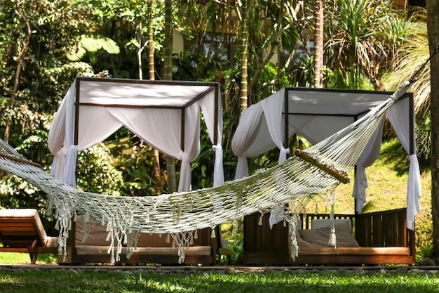 인도네시아 발리 섬의 아름다운 열대 정원에서 휴식과 휴식의 장소 인 아늑한 전망대의 테이블에 해먹, 수평 방향