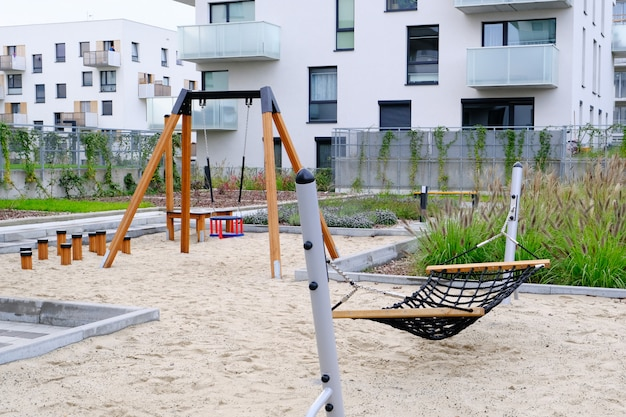Hammock and swing on a children playground in cozy courtyard of modern residential district.