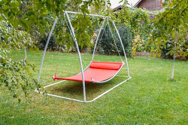 집 코티지 근처 뒤뜰에 있는 녹색 잔디에 아무도 없는 금속 프레임의 해먹 스윙. 여름 정원의 레드 해먹 스윙에서 혼자 휴식을 취하세요.