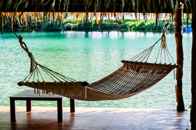 A hammock in the wooden cottage on the sea
