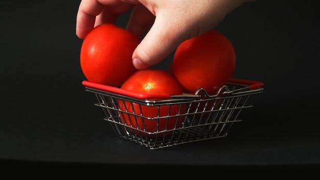 店の小さなバスケットにトマトを並べて集める男性の手
