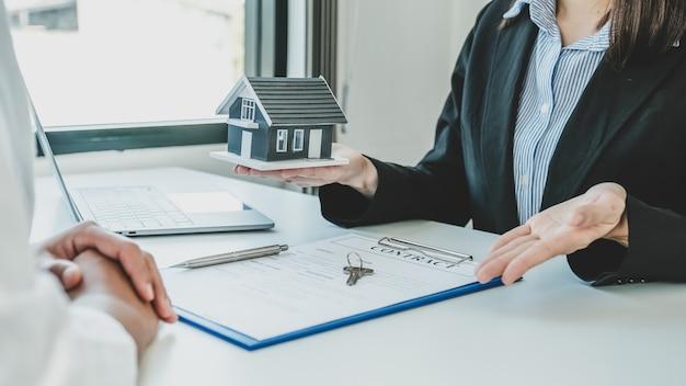 Дайте агенту по недвижимости держать модель дома и объяснить женщине-покупателю деловой договор, аренду, покупку, ипотеку, ссуду или страхование жилья.