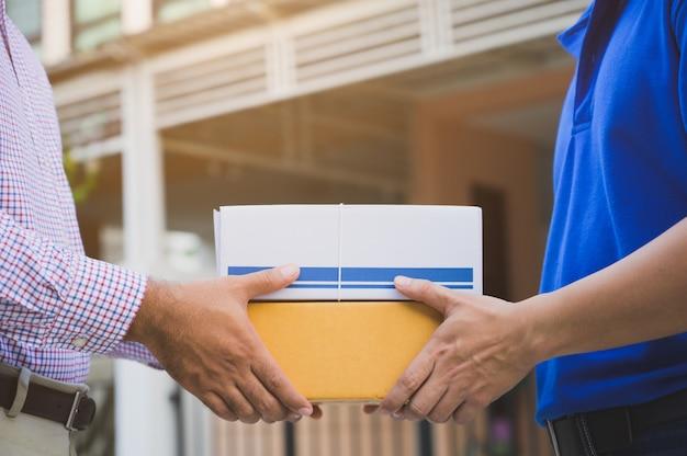 Рука принимает доставку коробок от доставщика.