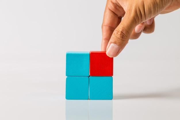 最後に欠けていた木製のブロックを所定の位置に手で追加します。ビジネスの成功の概念。