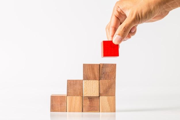 Рука вставляет последний недостающий деревянный блок на место. концепция успеха в бизнесе.
