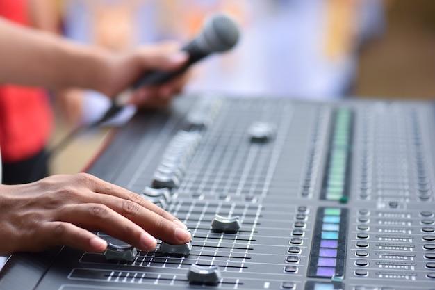 コンサートミキサーコントロール音楽エンジニアの舞台裏でのハンドアジャストサウンドチェック