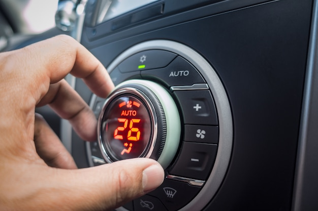 Hand adjusting air conditioner button at 26 degree in the vehicle or car for comfortable