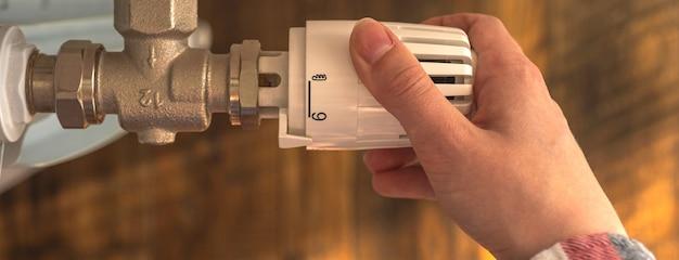 Ручная регулировка температуры с помощью термостата радиатора дома, фото баннера