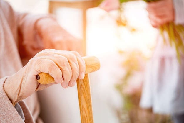 Hand of aged woman with cane on light