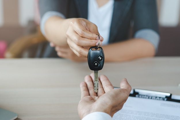 Hand of agent giving car key to customer after signed rental contract form.